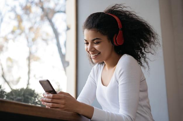 携帯電話を使用して、オンラインでビデオを見て、音楽を聴いて、家で座っているアフリカの女性