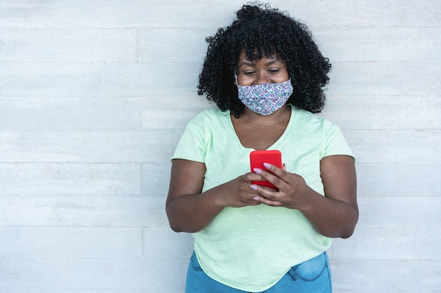 保護フェイスマスクを着用しながら携帯電話を使用しているアフリカの女性
