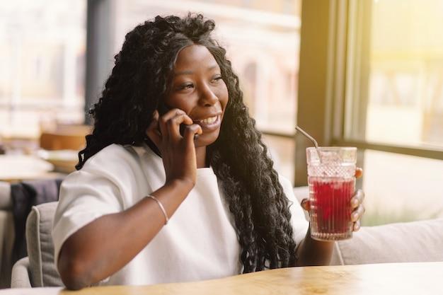 Африканская женщина с помощью телефона в кафе.