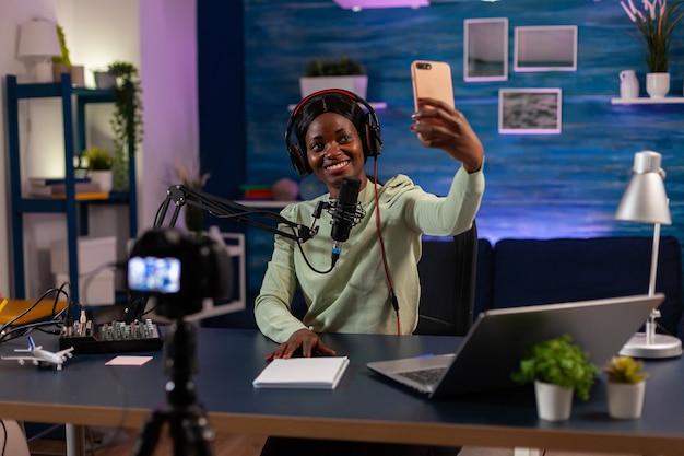 엔터테인먼트 비즈니스 녹화 에피소드에서 스마트폰을 사용하여 사진을 찍는 아프리카 여성. 온에어 온라인 제작 인터넷 팟캐스트 쇼 호스트 스트리밍 라이브 콘텐츠, 디지털 소셜 미디어 녹음.