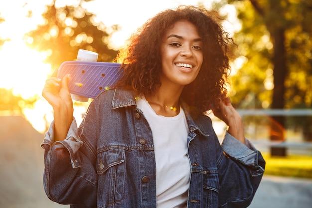 スケートボードを持って公園で屋外を歩くアフリカの女性。