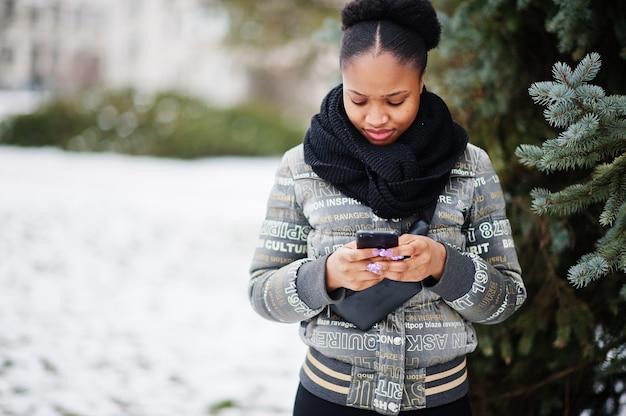 손에 휴대 전화와 함께 유럽에서 겨울 날에 검은 스카프 스탠드 neae 새 해 나무에 아프리카 여자 착용.