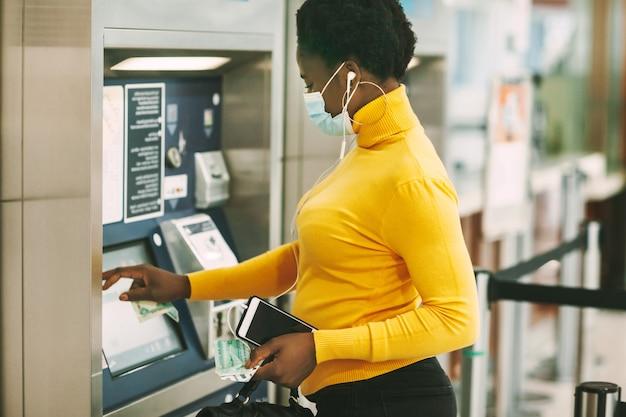 보호 마스크를 쓰고 아프리카 여성은 atm에서 은행 카드에서 돈을 인출합니다.