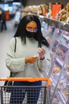 Африканская женщина в одноразовой медицинской маске. покупки в супермаркете во время вспышки пандемии коронавируса. время эпидемии.