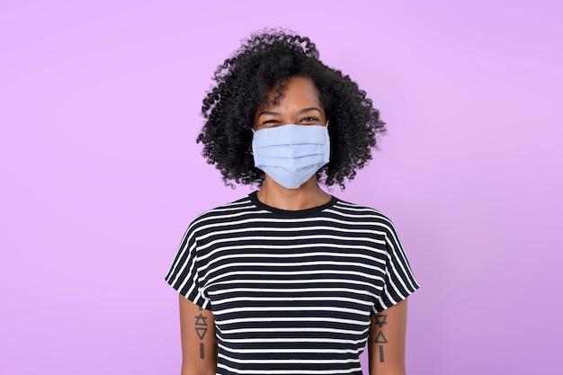 Donna africana che indossa una maschera facciale nella nuova normalità