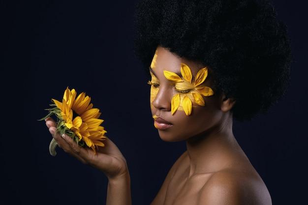 Африканская женщина с подсолнухом и креативный макияж на лице