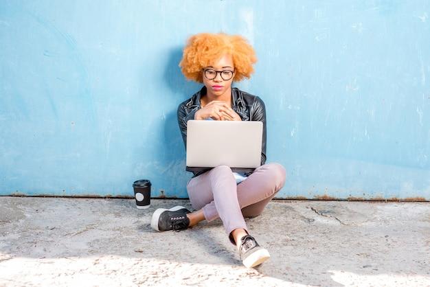Африканская женщина с вьющимися волосами работает с ноутбуком, сидя на синем фоне стены