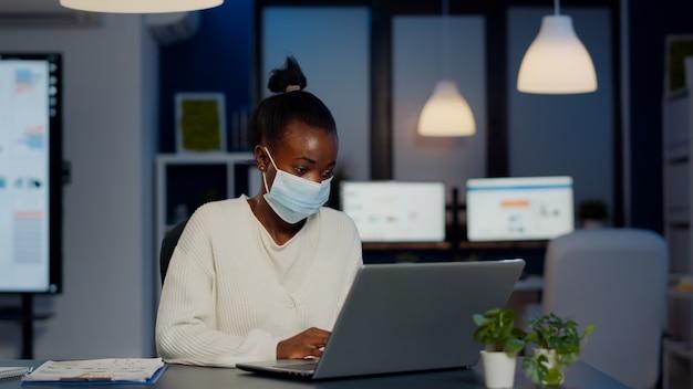 얼굴 마스크를 가진 아프리카 여성은 늦은 밤에 이메일을 읽고 새로운 일반 비즈니스 사무실에서 작업하는 프로젝트의 기한을 존중하고 문서를 분석하고 글로벌 유행병 동안 전략을 수립합니다.