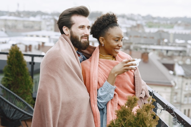 African woman with husband. guy and girl in a plaid. lovers drinking coffee on balcony.