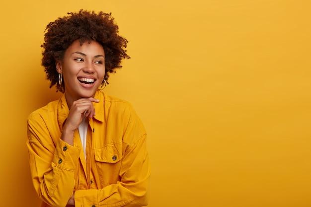 La donna africana con una bellezza naturale, un'espressione spensierata, guarda da parte, ha un atteggiamento amichevole e felice
