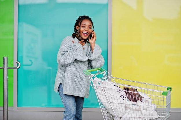 ショッピングカートトロリーを持つアフリカの女性は屋外市場を提起し、電話で話します。