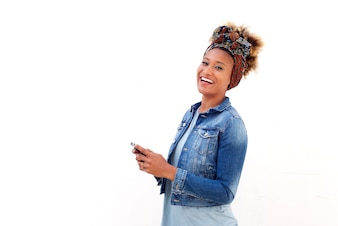 African woman with smart phone standing against white background and laughing