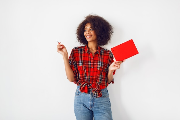 African woman with surprise face holding notebook and pointing up. funny emotions. white background.