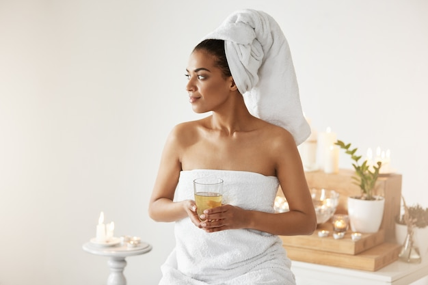 African woman with towel on head holding glass smiling looking in side resting in spa resort.