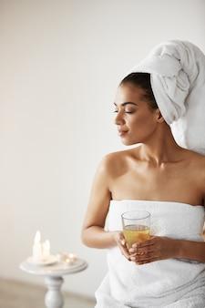 Donna africana con l'asciugamano sullo sguardo sorridente di vetro della tenuta capa nel riposo laterale nella località di soggiorno di stazione termale.