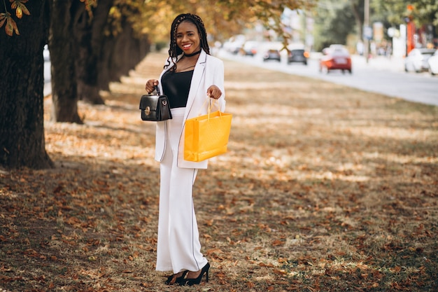 African woman with yellow shopping bags in park
