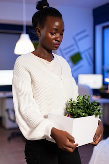悲しい、落ち込んだ表情で仕事から解雇されたオフィスのカーボードを保持しているアフリカの女性労働者
