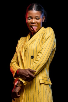 African woman in yellow jacket having her tongue out