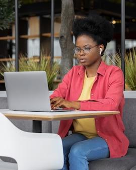 ノートパソコンで作業しているコワーキングルームでピンクのシャツを着た若くて美しいアフリカの女性