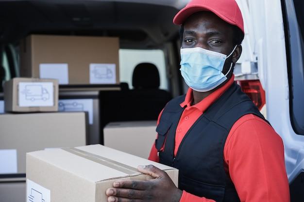 코로나 바이러스 발생 중 안전 마스크를 착용하는 동안 상자를 배달하는 아프리카 노동자-얼굴에 초점