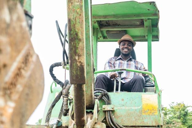 Африканский рабочий с улыбкой и счастливым за рулем тяжелой строительной техники