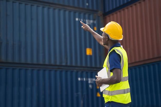 Африканский рабочий держит планшет, идет и проверяет коробку контейнеров с грузового корабля для экспорта и импорта