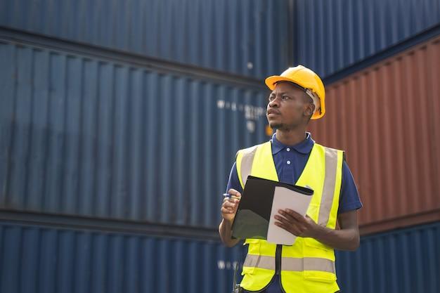 Африканский рабочий держит документ, идет и проверяет коробку контейнеров с грузового корабля для экспорта и импорта