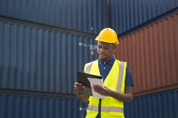 African worker holding document, walking and checking the containers box from cargo ship for export and import