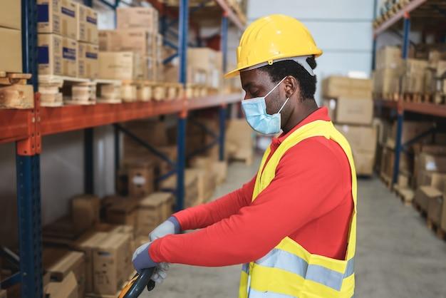 倉庫店でパレットトラックを引っ張るアフリカの労働者の男-顔に焦点を当てる
