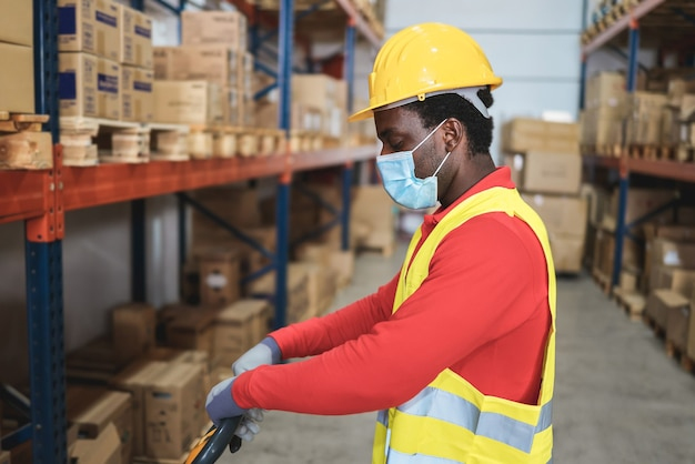 African worker man pulling a pallet truck at warehouse store - focus on face