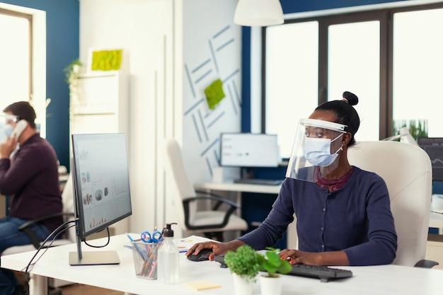 Африканец, работающий на рабочем месте, носит маску против covid19 в качестве меры предосторожности. многонациональная команда в новом обычном финансовом офисе проверяет отчеты, анализирует данные, глядя на рабочий стол. новый