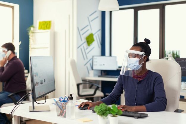 Africano che lavora sul posto di lavoro indossando una maschera facciale contro il covid19 come precauzione di sicurezza. team multietnico nel nuovo normale ufficio finanziario aziendale che controlla i rapporti, analizza i dati guardando il desktop. nuovo