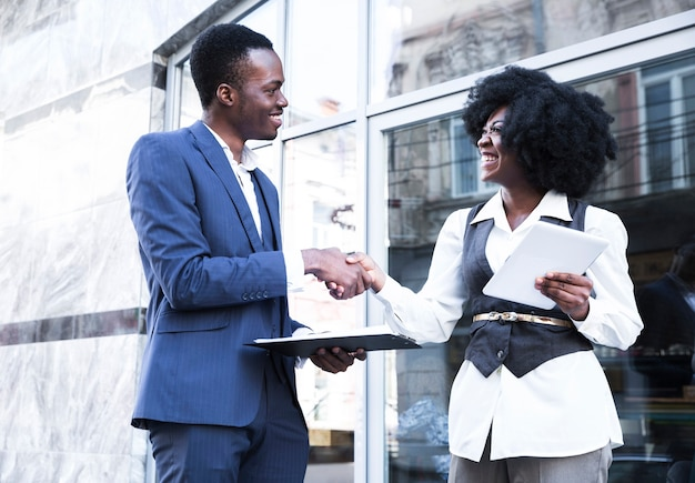 An african young businessman and businesswoman shaking hands