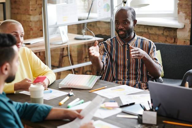 Африканский молодой бизнесмен, сотрудничающий за столом вместе со своими коллегами во время деловой встречи