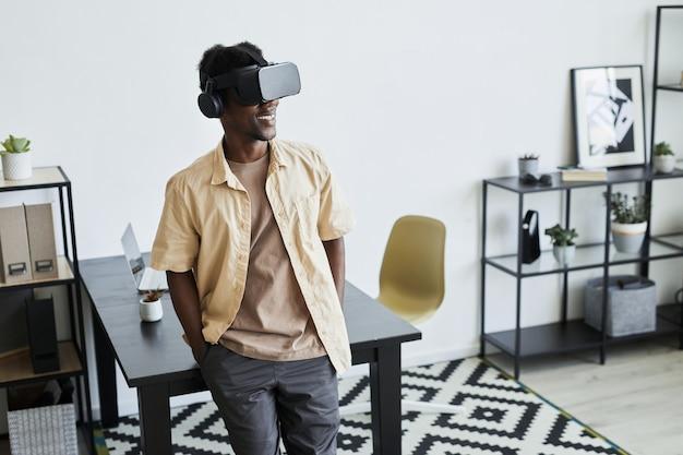 사무실에 서 있는 동안 온라인으로 작업하는 가상 현실 안경을 쓴 아프리카 젊은 사업가