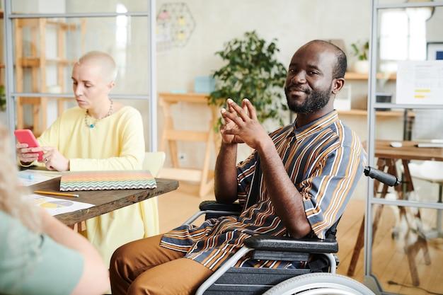 Африканский молодой бизнесмен в инвалидной коляске, глядя в камеру, сидя на встрече в офисе