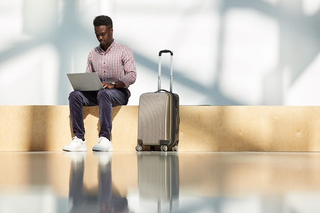 African young businessman sitting at the airport with luggage and working on laptop while waiting for his flight