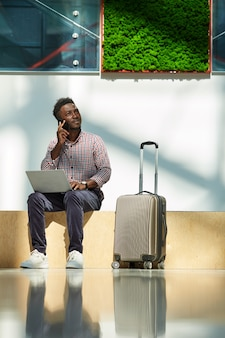 African young businessman talking on mobile phone and uisng laptop while sitting at the airport he ordering plane tickets