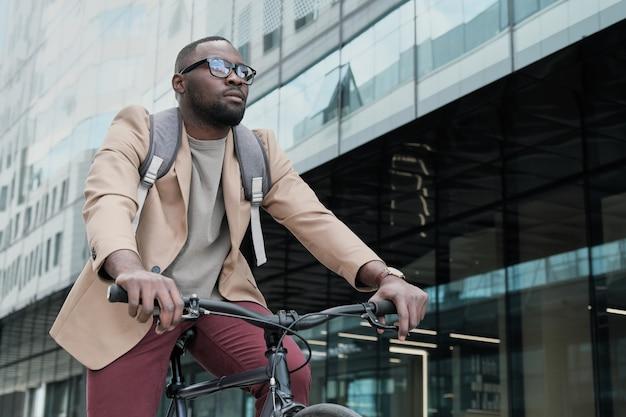 Африканский молодой бизнесмен с рюкзаком за спиной, едущий на велосипеде в городе