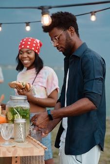 샌드위치와 함께 점심을 먹고 야외에서 레모네이드를 마시는 아프리카 젊은 부부