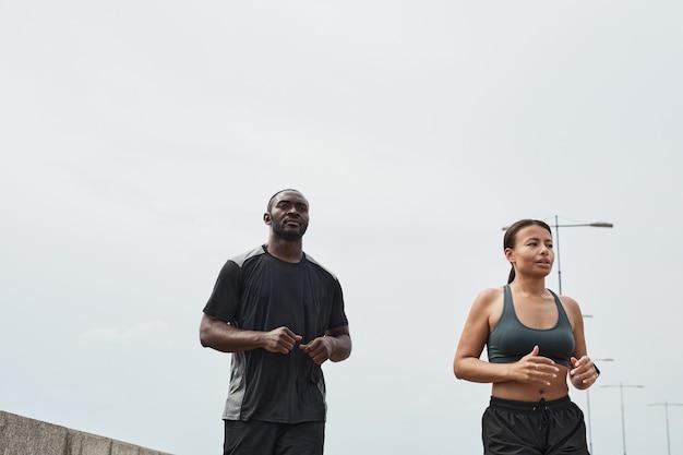 青い空を背景に屋外で朝一緒に走っているアフリカの若いカップル