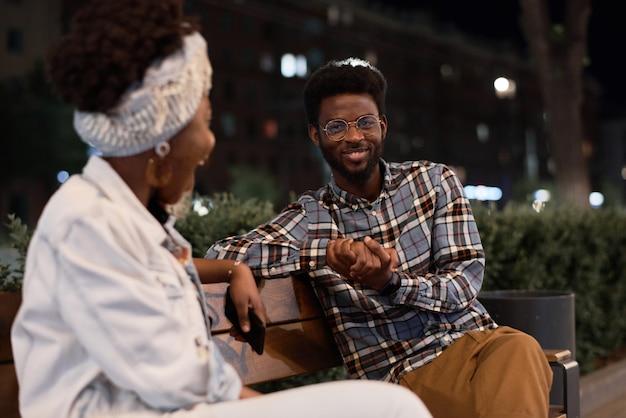 ベンチに座って、公園でデート中に話しているアフリカの若いカップル