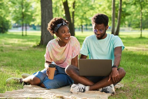 コーヒーを飲み、公園でラップトップコンピューターを使用して草の上に座っているアフリカの若いカップル