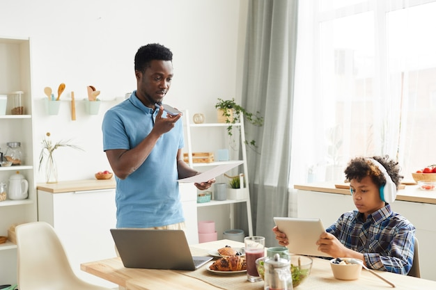 African young father talking on the phone and examining documents he working at home while his son playing games on digital tablet in the kitchen