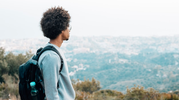 An african young male hiker with his backpack looking at view