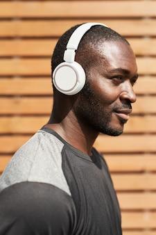 屋外に立って音楽を楽しんでいるワイヤレスヘッドフォンでアフリカの若い男