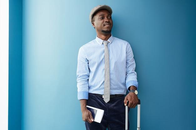 青い壁に寄りかかってスーツケースとチケットを持って立っているアフリカの若い男と彼は旅行するつもりです