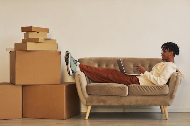 ノートパソコンでソファに横になり、出荷の準備ができている床に小包の大きなスタックでオンライン注文を処理しているアフリカの若い男
