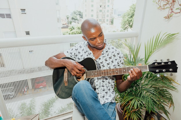 African young man playing the guitar sitting in the balcony