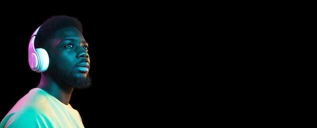 コピースペースと暗い壁の上のヘッドフォンでアフリカの若い男の肖像画